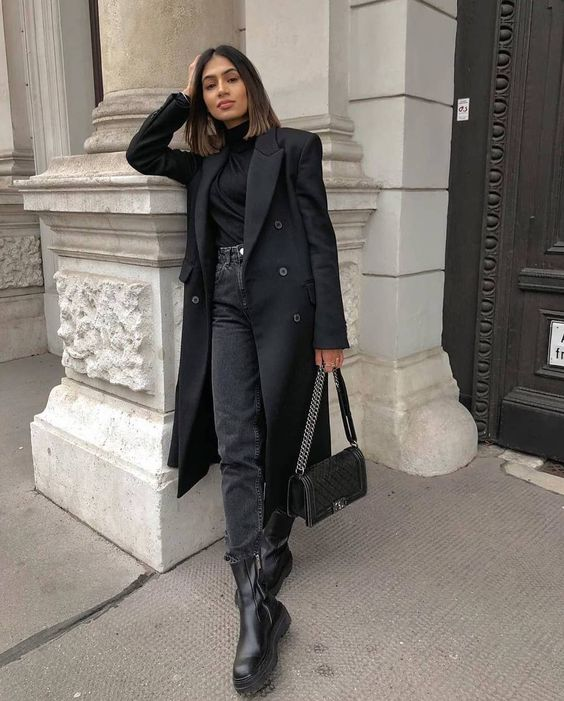 a monochromatic outfit with a black turtleneck, grey jeans, black combat boots, a black trench and a black bag