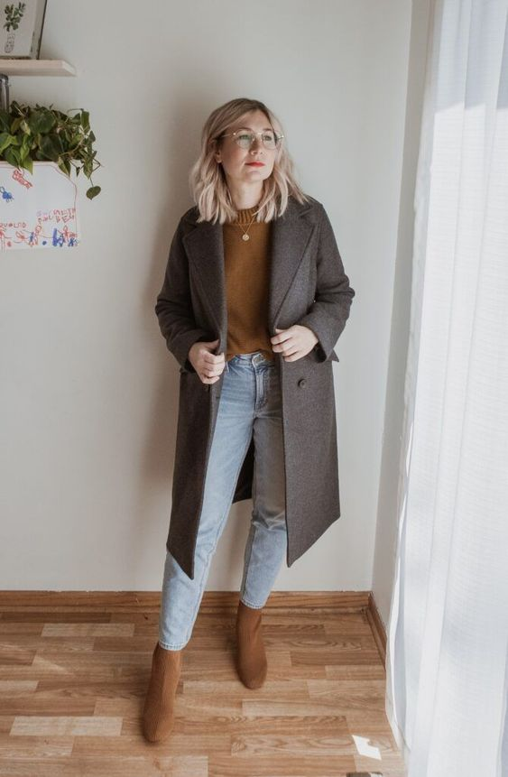 a mustard jumper, blue jeans, rust-colored boots, a grey midi coat and a chain necklace for a chic fall look