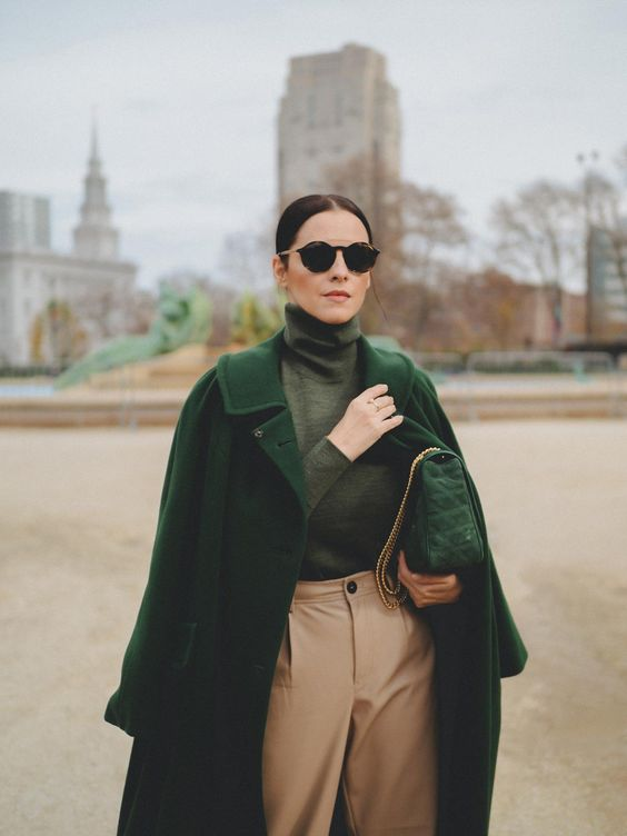 a muted grene turtleneck, an emerald coat, tan pants, a green bag to rule the fall colors