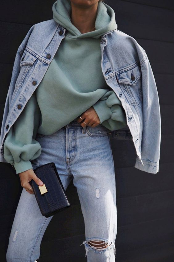 a pale green oversized hoode, blue ripped jeans and an oversized bleached blue denim jacket plus a black clutch