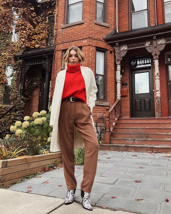 a red turtleneck sweater, brown pants, snakeskin print booties, a creamy short coat for a cold fall day