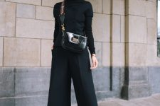 a refined outfit with a black turtleneck and a waistcoat with buttons, culottes, lacquer boots and a matching bag
