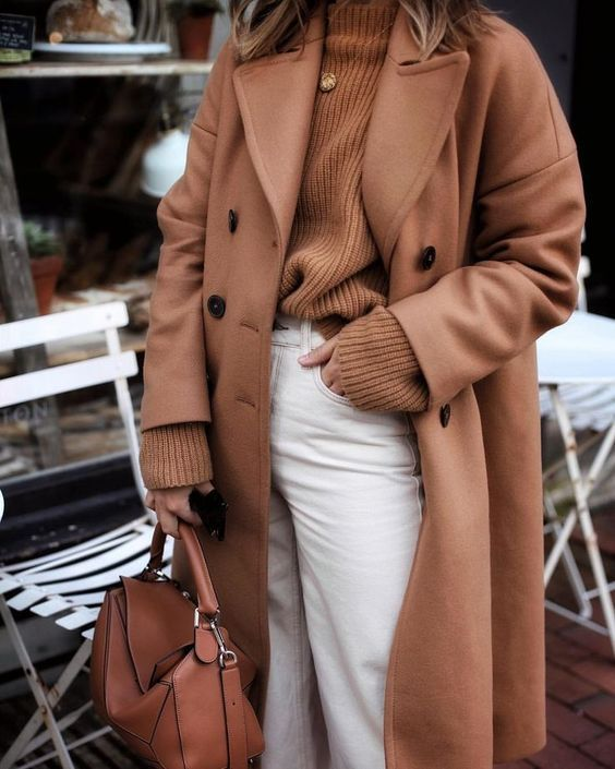 a rust-colored fall outfit with a sweater, a midi coat, white jeans and a bag is a great idea for a cold fall day