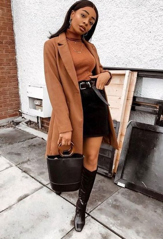 a rust ribbed turtleneck, a black mini skirt, black knee boots, a rust knee coat and a black bucket bag for a chic look