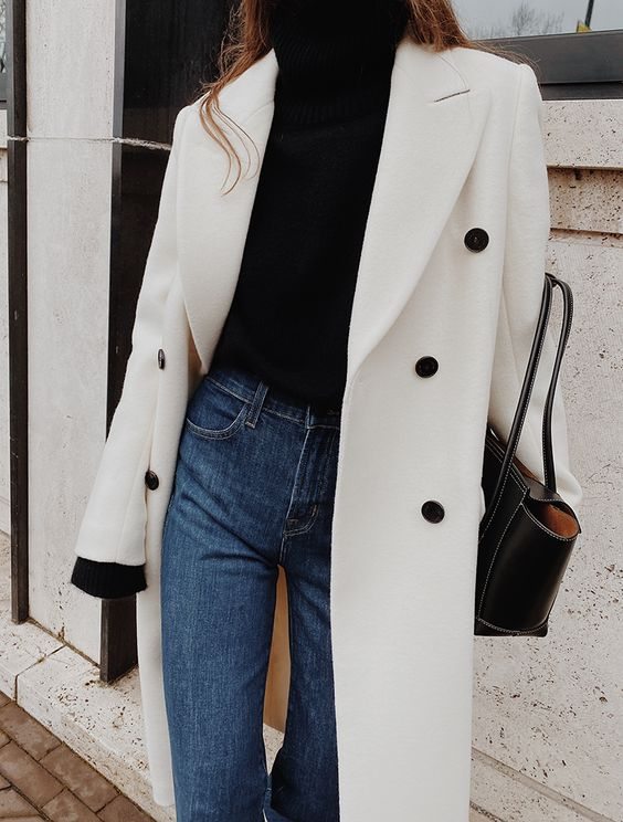 a simple and contrasting look with a black turtleneck, blue high rise jeans, a white coat with black buttons and a black tote