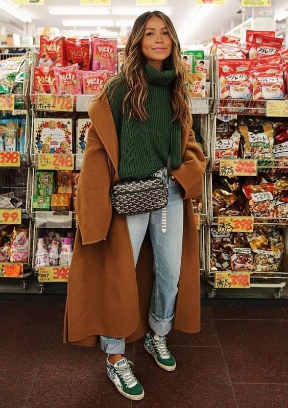 a simple and lovely fall look with a green turtleneck sweater, blue jeans, green trainers, a brown coat and a printed bag