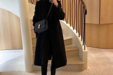 a simple total black look with a turtleneck, skinnies, platform boots, a midi coat and a comfy bag