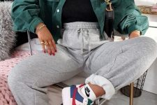 a sport chic look with a black turtleneck, grey sweatpants, colorful trainers, a green denim cropped jacket and a necklace