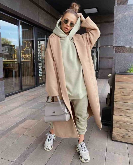 a sporty look with a light green hoodie and sweatpants, grey trainers, a tan coast and a grey coat for the fall