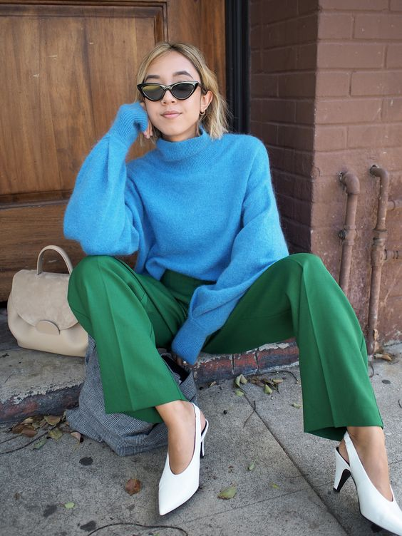 a stylish and cozy fall look with a bold blue sweater, bold green trousers, white slingbacks and a neutral bag is cool
