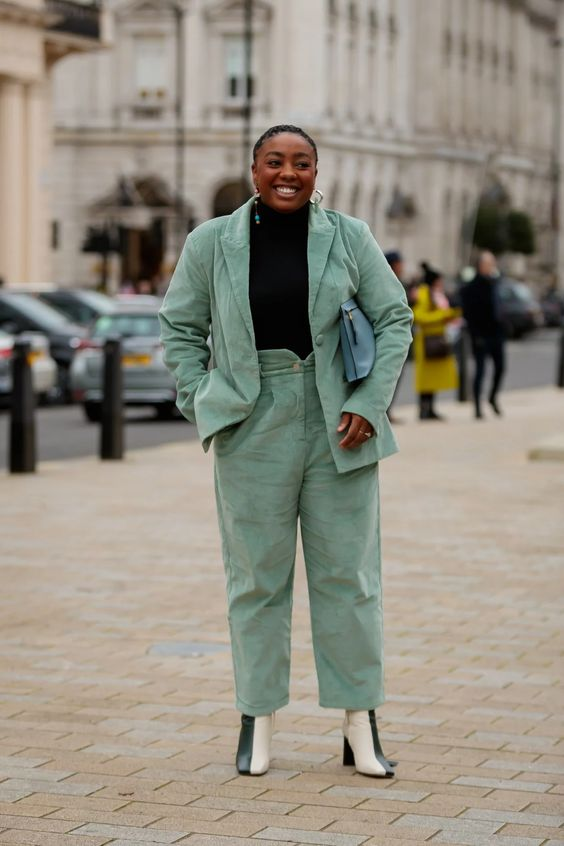 a stylish work outfit with a pale green pantsuit, a black turtleneck, two color boots and a light blue bag