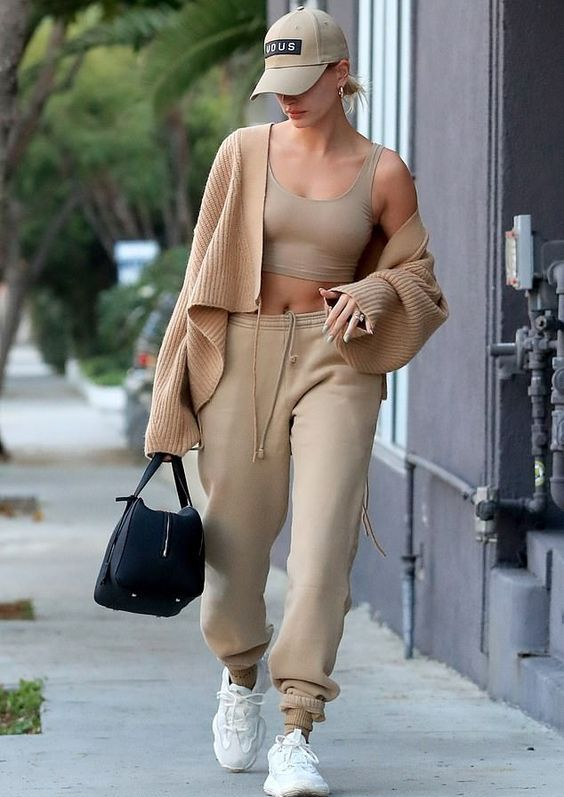 a tan crop top and sweatpants, white trainers, a beige cardigan, a black bag and a tan cap is cool