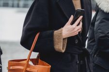 a taupe turtleneck sweater, a black coat and an amber bucket bag for a touch of color on a cold fall day