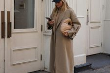 a total beige look with a turtleneck, trousers, a midi coat, white sneakers and a cap plus a beige bag