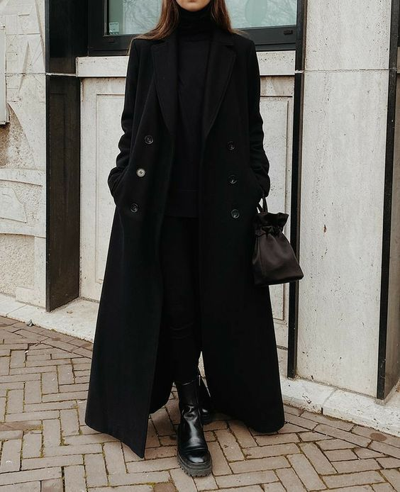 a total black look with a turtleneck, skinnies, chunky boots, a maxi coat and a bucket bag