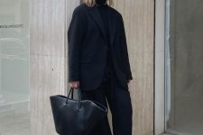 a total black look with a turtleneck, wide leg trousers, platform shoes, an oversized blazer and a tote for work or for every day