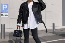 a total black outfit with an oversized leather jacket, skinnies, black boots, a mini bag is refreshed with an oversized white shirt