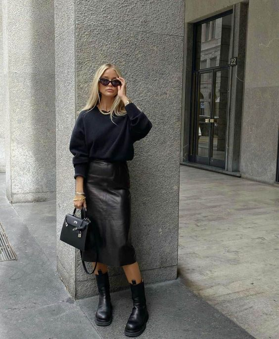 a total black work look with a sweatshirt, a plain leather midi skirt, chunky boots and a bag
