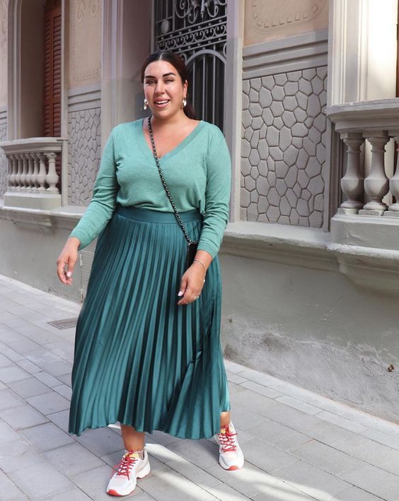 a total green look with a light green jumper, a dark green pleated maxi skirt, white trainers and a black bag
