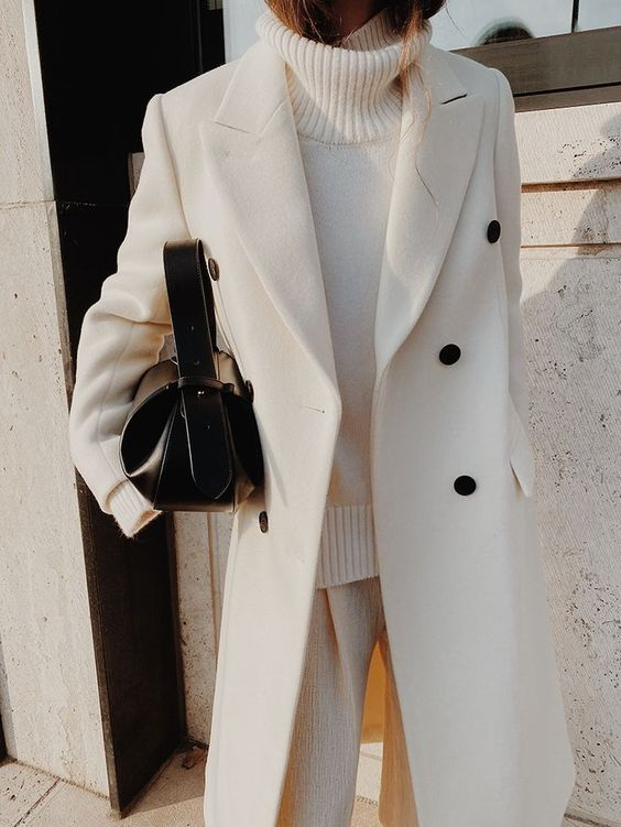 a total white look with a turtleneck sweater, trousers, a coat with black buttons and a black mini bag