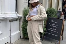 a very simple look with a white crop top, tan sweatpants and an oversized blazer, white trainers and a bucket hat