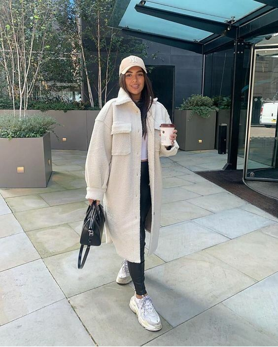 a white crop top, black leather leggings, white trainers, a white midi shirt jacket and a cap, a black bag for a contrasting look