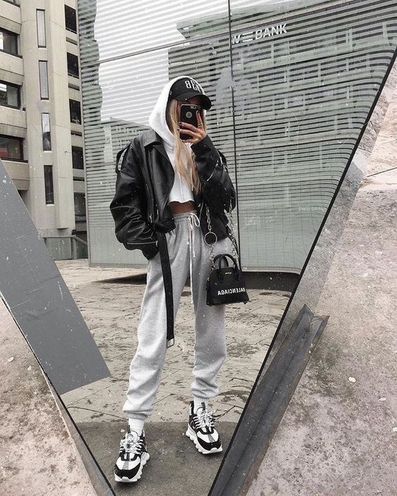 a white cropped hoodie, grey sweatpants, black and white trainers, a black leather jacket, a cap and a black bag