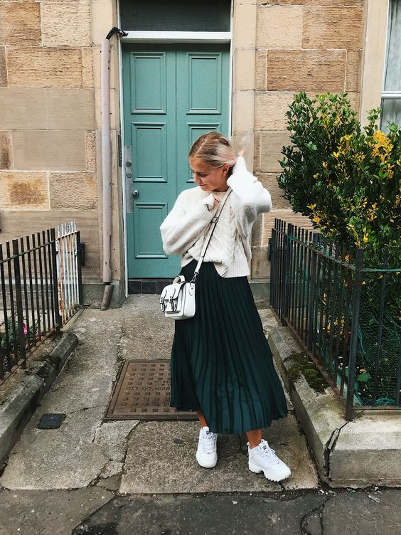 a white patterned sweater, white trainers and a bag plus a dark green plated maxi skirt for a bold contrast