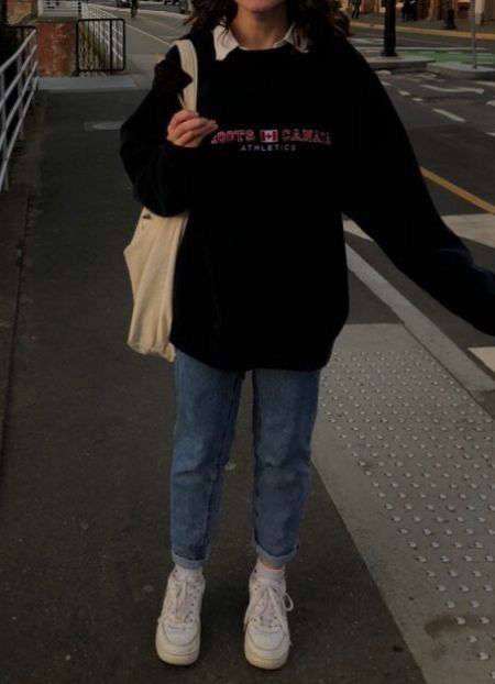 a white shirt, an oversized black hoodie, blue jeans, white trainers and a canvas tote for a simple college look