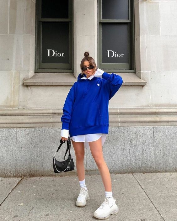 a white shirtdress, an electric blue oversized hoodie, white socks and trainers and a black bag for a cool and edgy outfit