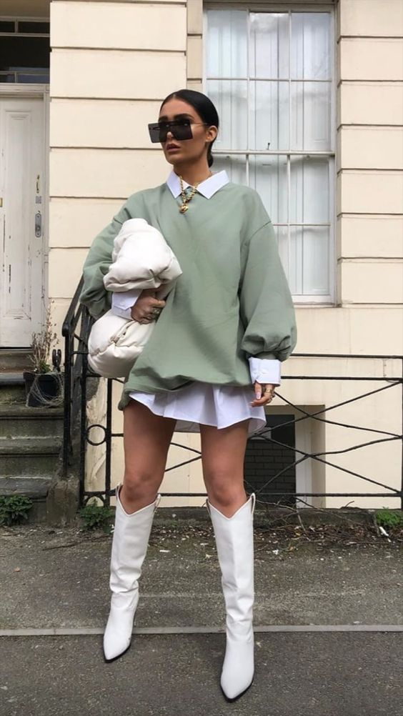 a white shirtdress, an olive green oversized sweatshirt, white boots, a white bag and a statement necklace for a trendy look