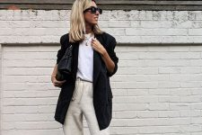 a white t-shirt, an oversized black blazer, neutral sweatpants, white trainers, a black bag and layered necklaces