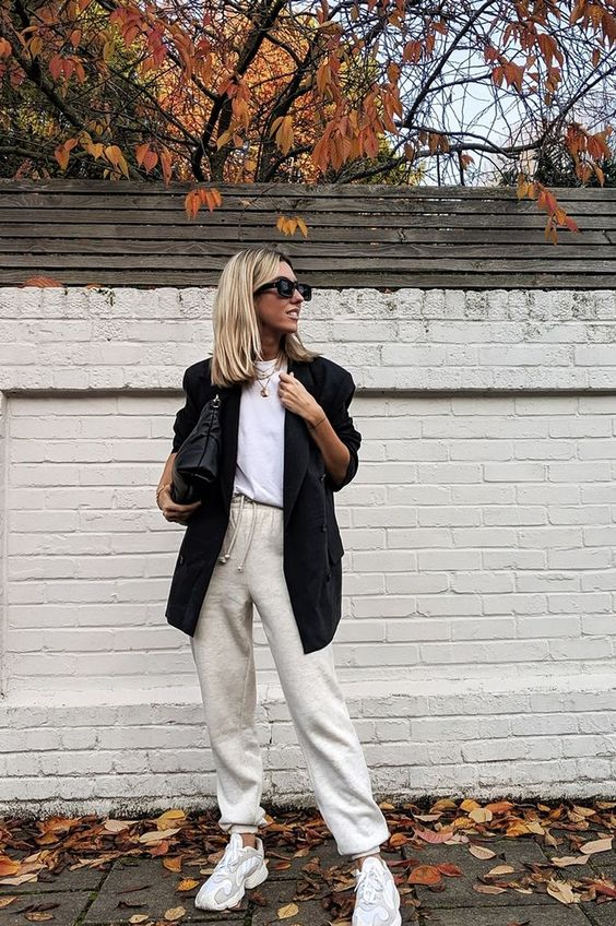 a white t shirt, an oversized black blazer, neutral sweatpants, white trainers, a black bag and layered necklaces