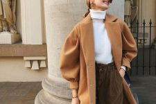 a white turtleneck, rust high waisted pants, a beige coat and statement earrings to look chic on a cold day