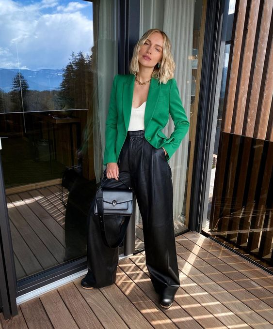 an elegant and bold fall work look with a white top, a fitting green blazer, black leather trousers, black boots and a bag