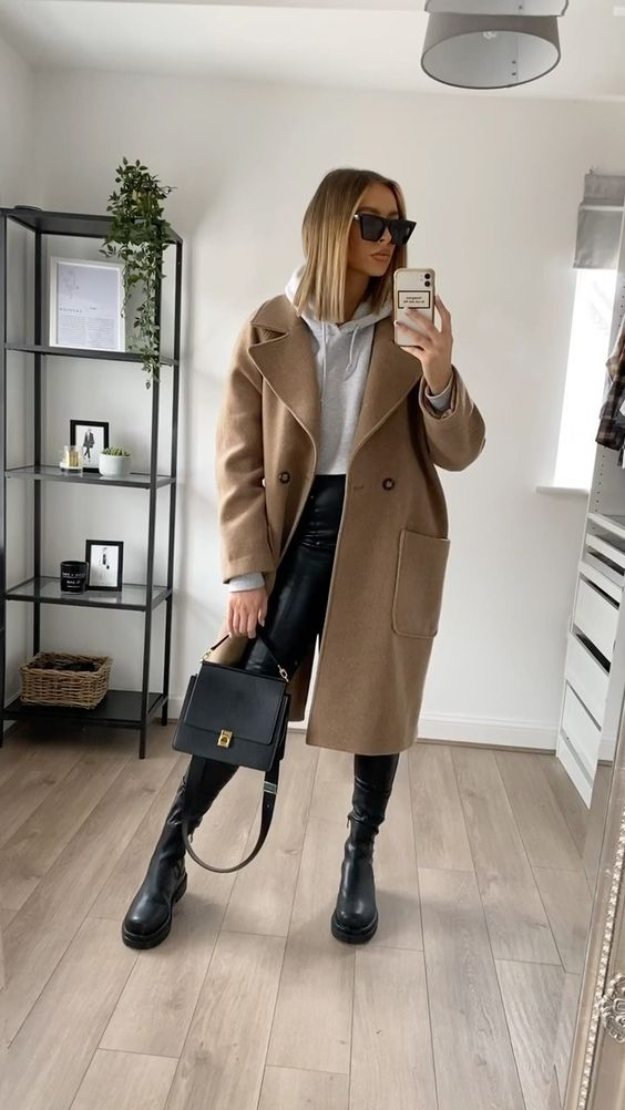 an everyday outfit with a grey hoodie, leather leggings, boots, a tan midi coat, a black bag for the fall