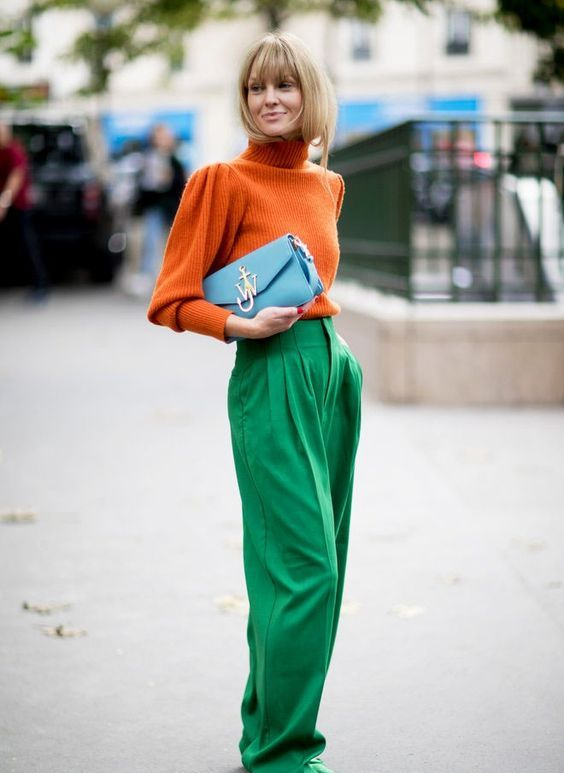 an orange turtleneck, emerald trousers, emerald shoes and a pale blue clutch for a work look