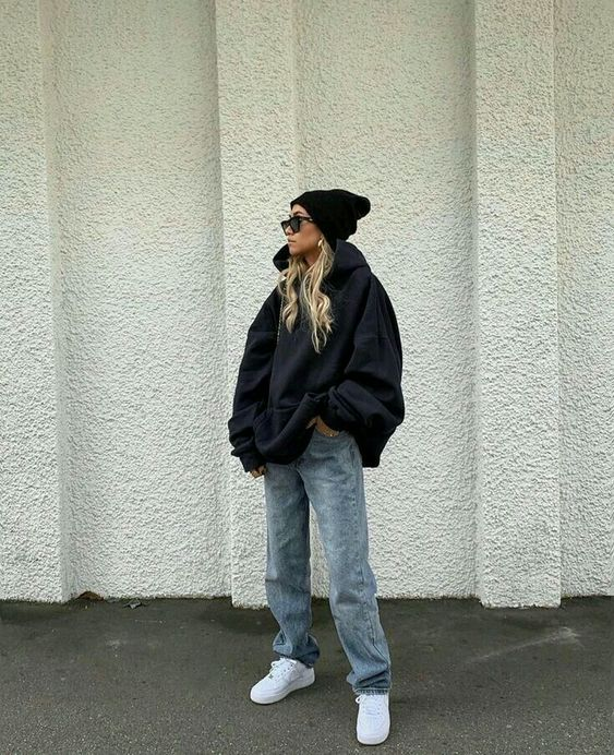 an oversized black hoode, blue jeans, white sneakers, a black hoodie for a super cozy fall outfit