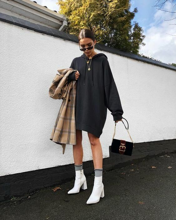an oversized black hoodie, grey socks, white boots and a black bag plus a tan plaid trench for colder weather
