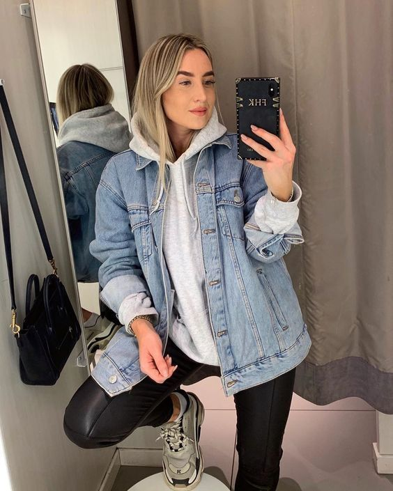 an oversized grey hoodie, black leather leggings, grey trainers and a light blue oversized denim jacket