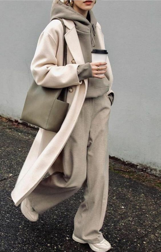 an oversized grey hoodie tucked into matching rey trousers, white trainers, a white coat and a grey tote to wear right now