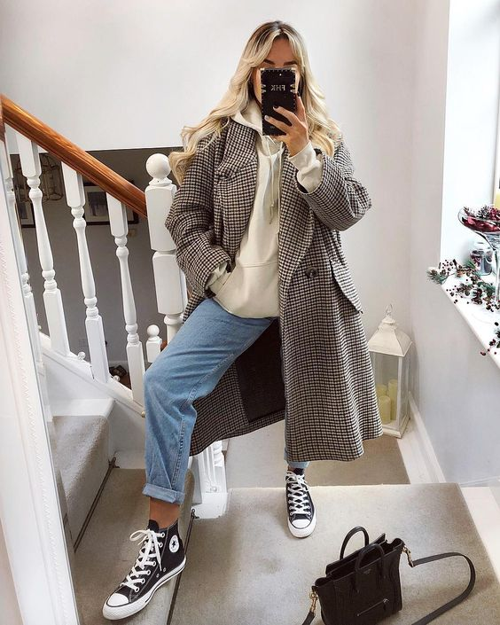 an oversized neutral hoodie, blue jeans, a plaid midi coat, black sneakers and a black bag