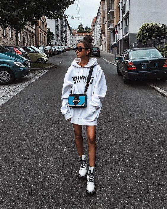 an oversized white hoodie as a mini dress, white combat boots, a blue and black crossbody bag - nothing else is needed