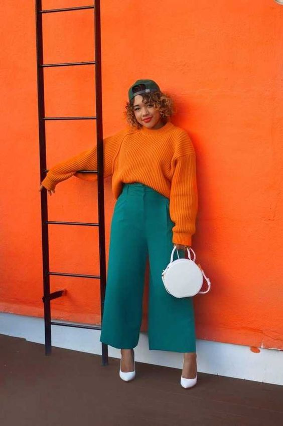 an unexpected color combo of an orange sweater, green culottes, white shoes and a white bag for a statement