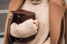 black jeans, a tan turtleneck sweater, a bege coat, a brown reptile print bag for a cold day