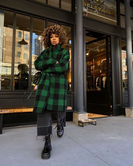 black straight jeans, black combat boots, a green and black plaid midi coat and a black bag for a comfy fall look