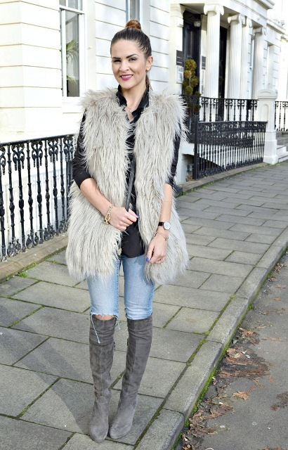 With black shirt, distressed jeans, faux fur vest and bag