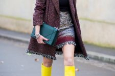 With black turtleneck, fringe mini skirt and emerald clutch