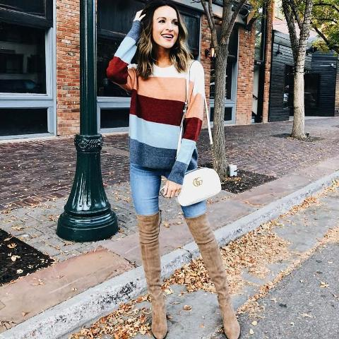With color block sweater, skinny jeans and white bag