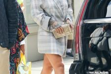 With metallic clutch, light gray high heels and rounded sunglasses
